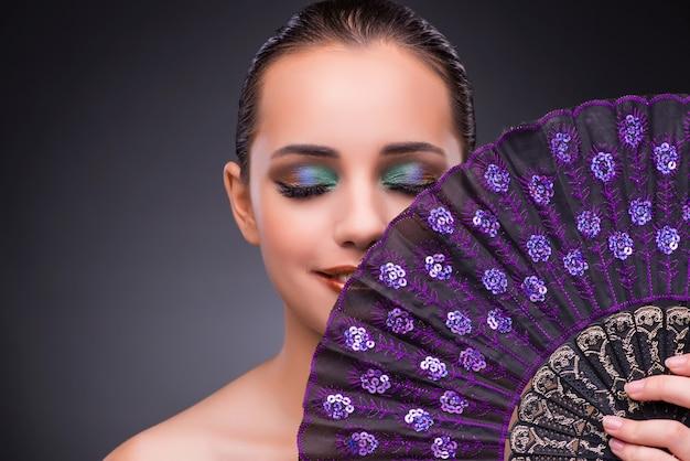Mulher bonita com ventilador no conceito de moda