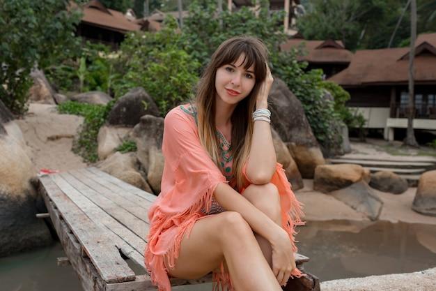 Mulher bonita com vestido boho posando perto de resort de luxo. enjoing férias na ilha tropical.