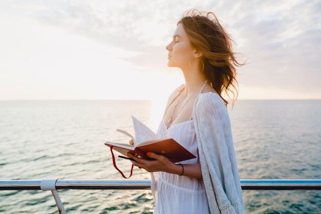 Mulher bonita com vestido branco de verão caminhando à beira-mar ao nascer do sol com livro diário em clima romântico pensando e fazendo anotações