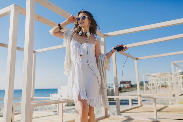 Mulher bonita com vestido branco de verão ouvindo música em fones de ouvido, dançando e se divertindo, segurando o smartphone, estilo de férias de verão praia