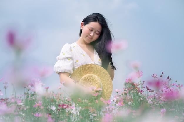 Mulher bonita com vestido branco e céu azul pastel no jardim de flores
