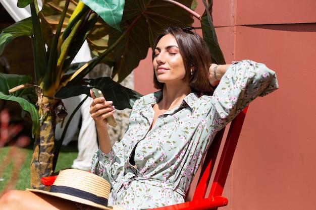 Mulher bonita com vestido de verão sentada na cadeira no quintal em um dia de sol com telefone celular