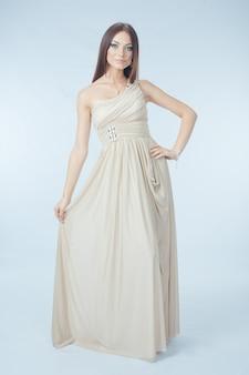 Mulher bonita com vestido moderno posando no estúdio