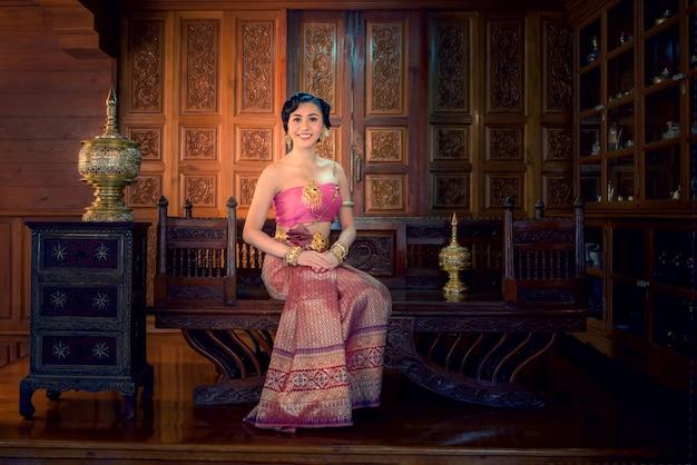 Mulher bonita com vestido tailandês sentado no howdah na casa de estilo antigo de madeira tailandês