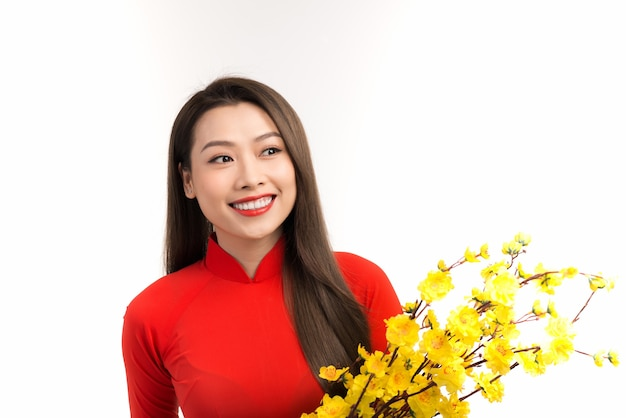 Mulher bonita com vestido tradicional da cultura vietnamita, segurando flor de damasco sobre branco