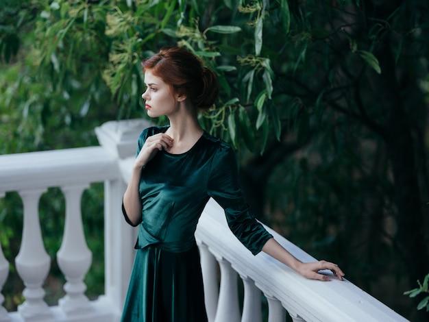 Mulher bonita com vestido verde charme estilo elegante ao ar livre