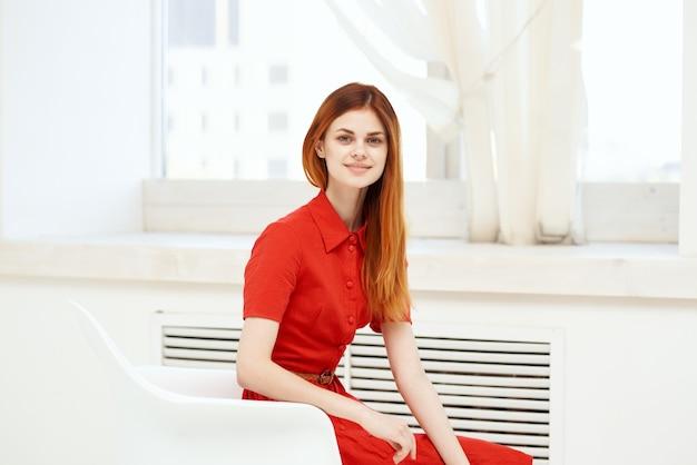 Mulher bonita com vestido vermelho sentada perto da janela em estilo elegante