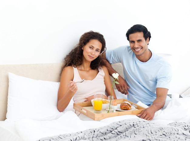 Mulher bonita comendo cereais para o café da manhã deitado na cama