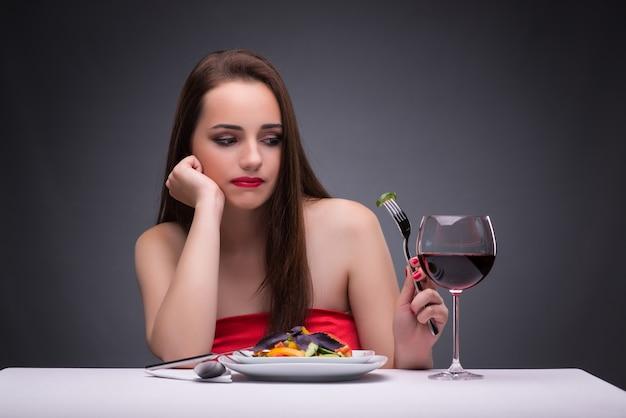 Mulher bonita comendo sozinha com vinho