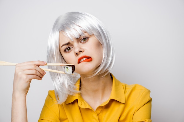 Mulher bonita comendo sushi e pãezinhos na entrega de comida na mesa