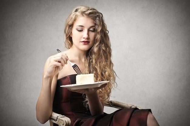 Mulher bonita comendo um bolo