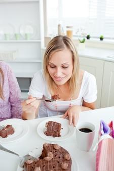Mulher bonita comendo um pedaço de bolo de chocolate sentado na cozinha