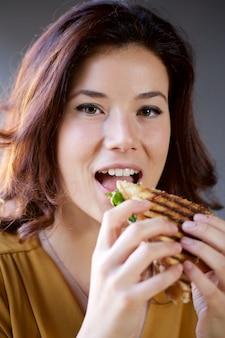 Mulher bonita comendo um sanduíche de clube em um restaurante de pub