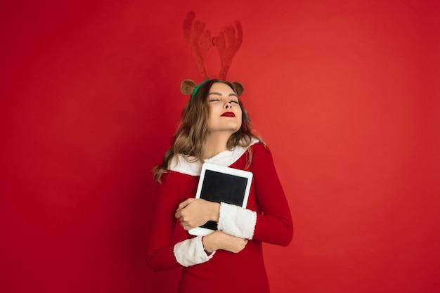 Mulher bonita como cervo de natal isolado na parede vermelha