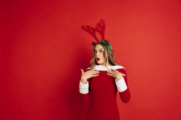 Mulher bonita como cervo de natal isolado na superfície vermelha, conceito de férias de clima de inverno de ano novo