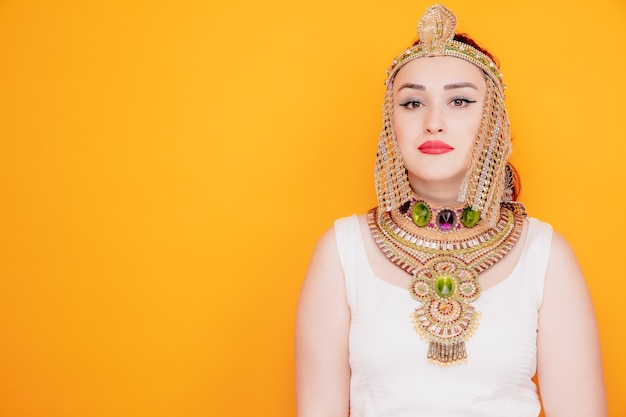 Mulher bonita como cleópatra em traje egípcio antigo com expressão séria e confiante em laranja