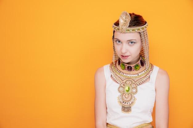 Mulher bonita como cleópatra em traje egípcio antigo olhando flertando sorrindo maliciosamente na laranja