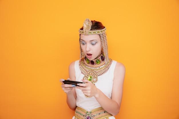 Mulher bonita como cleópatra em trajes egípcios antigos, jogando no smartphone maravilhada e surpresa em laranja