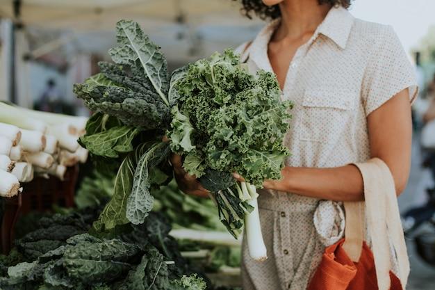 Mulher bonita comprando couve em um mercado de agricultores
