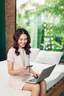 Mulher bonita, compras online com cartão de crédito em casa.