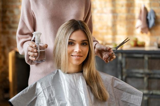 Mulher bonita cortando o cabelo em casa pelo cabeleireiro