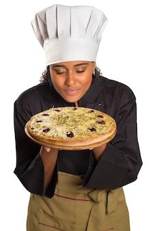 Mulher bonita cozinheira cheirando pizza de presunto no espaço em branco