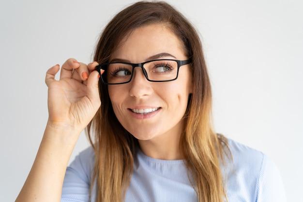 Mulher bonita curiosa ajustando os óculos e olhando para longe