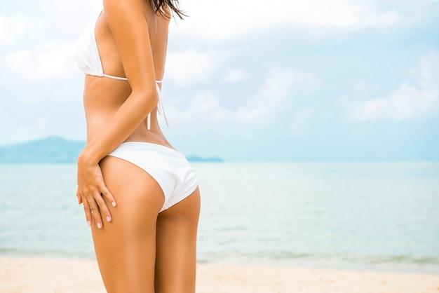 Mulher bonita da forma no roupa de banho branco do biquini que levanta na praia