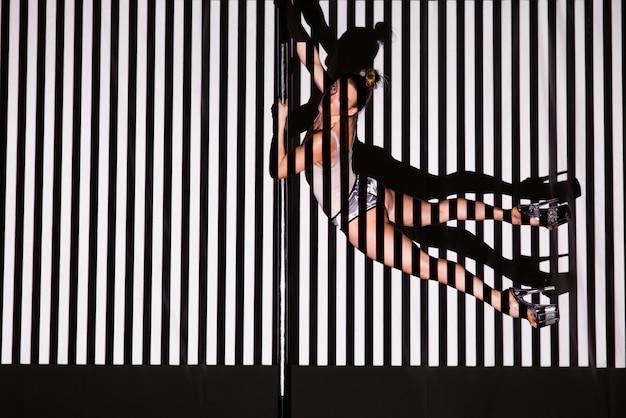 Mulher bonita dança perto de um poste em uma parede listrada