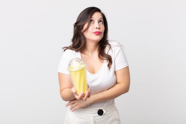 Mulher bonita dando de ombros, sentindo-se confusa e insegura e segurando um milkshake de baunilha