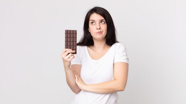 Mulher bonita dando de ombros, sentindo-se confusa e insegura e segurando uma barra de chocolate