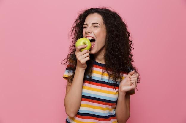 Mulher bonita de 20 anos com cabelo encaracolado comendo maçã verde isolada na rosa