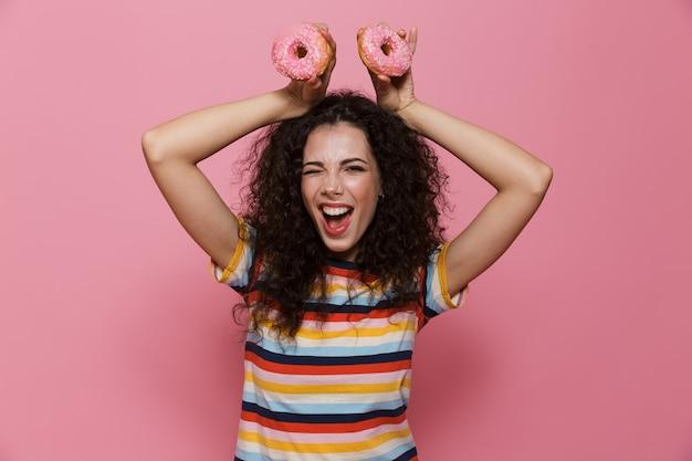Mulher bonita de 20 anos com cabelo encaracolado se divertindo e segurando rosquinhas isoladas em rosa