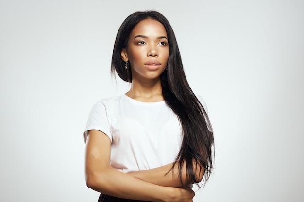 Mulher bonita de aparência africana em tshirt penteado na moda luz de fundo