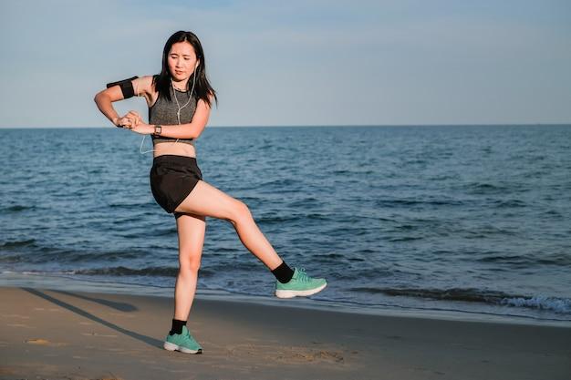 Mulher bonita de ásia em mercadorias do esporte que exercitam e que correm na praia.