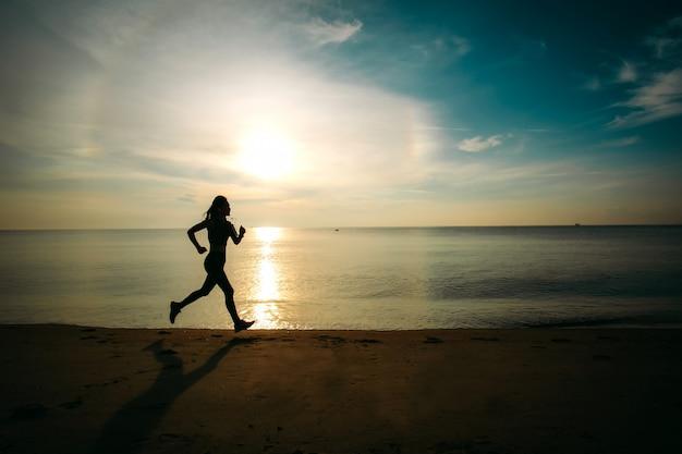 Mulher bonita de ásia no esporte ware pronto para o exercício, correndo na praia. estilo de silhueta.