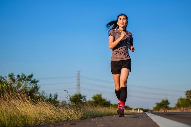 Mulher bonita de ásia nos mercadorias do esporte que correm na estrada conceito do exercício.
