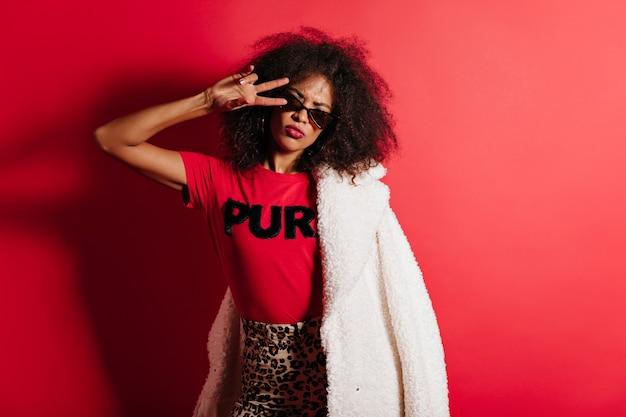 Mulher bonita de cabelo curto posando com o símbolo da paz na parede vermelha