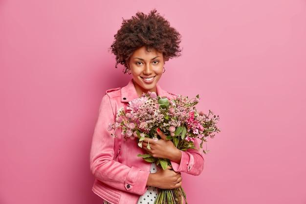 Mulher bonita de cabelo encaracolado abraça um grande buquê de flores recebido do namorado em clima festivo e usa uma jaqueta isolada sobre a parede rosa