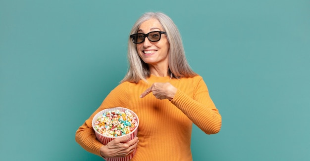 Mulher bonita de cabelo grisalho com balde de pipoca