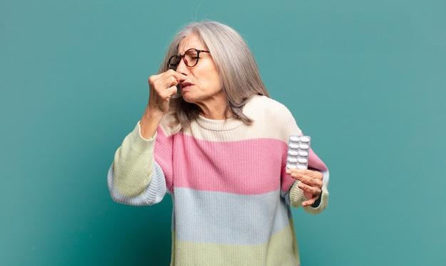 Mulher bonita de cabelo grisalho com remédios para doenças