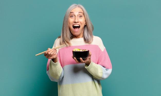 Mulher bonita de cabelo grisalho com uma tigela de ramen