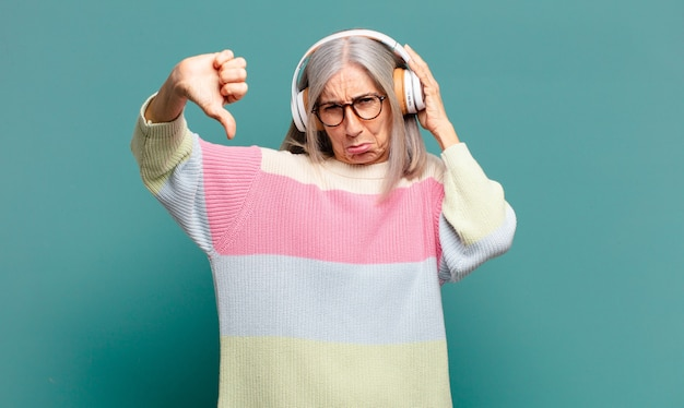 Mulher bonita de cabelo grisalho ouvindo música com fones de ouvido