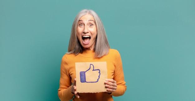 Mulher bonita de cabelo grisalho segurando uma mídia social como um banner