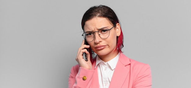 Mulher bonita de cabelo ruivo com um telefone inteligente
