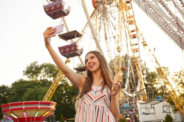 Mulher bonita de cabelos compridos positiva em pé sobre a roda gigante com casquinha de sorvete enquanto faz selfie em seu telefone celular, estando de bom humor e sorrindo alegremente
