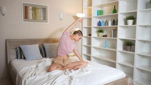 Mulher bonita de cabelos curtos em roupas esportivas fazendo yoga, sentada na cama durante o período de quarentena, auto-isolamento