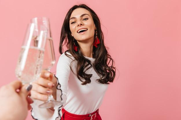 Mulher bonita de cabelos escuros com olhos azuis tilintando de óculos e sorrindo no fundo rosa.