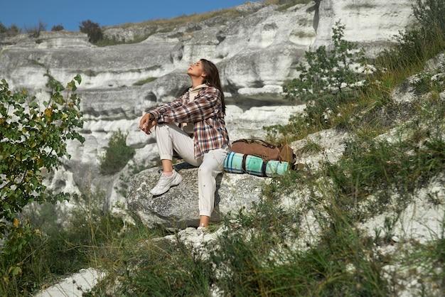 Mulher bonita de cabelos escuros em camisa quadriculada, sentado na pedra e aproveitando o dia de sol com os olhos fechados.