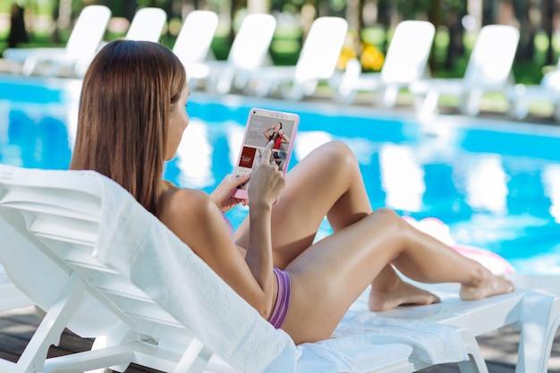 Mulher bonita de cabelos escuros fazendo compras on-line em seu tablet enquanto toma banho de sol perto da piscina